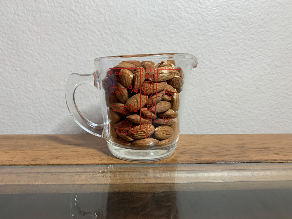 Raw Almonds in a measuring cup